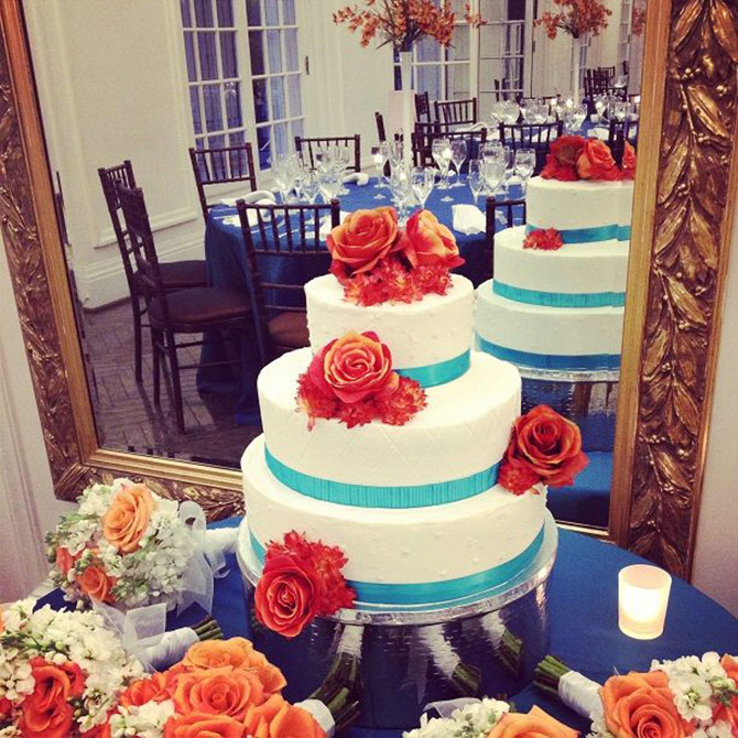 Main Event Caterers - Wedding cake orange roses and blue accents