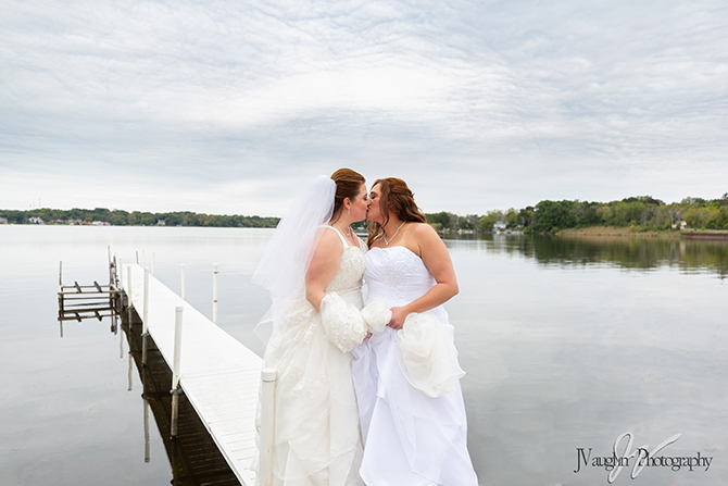 Lesbian brides on lake boat dock at Parkway Banquets
