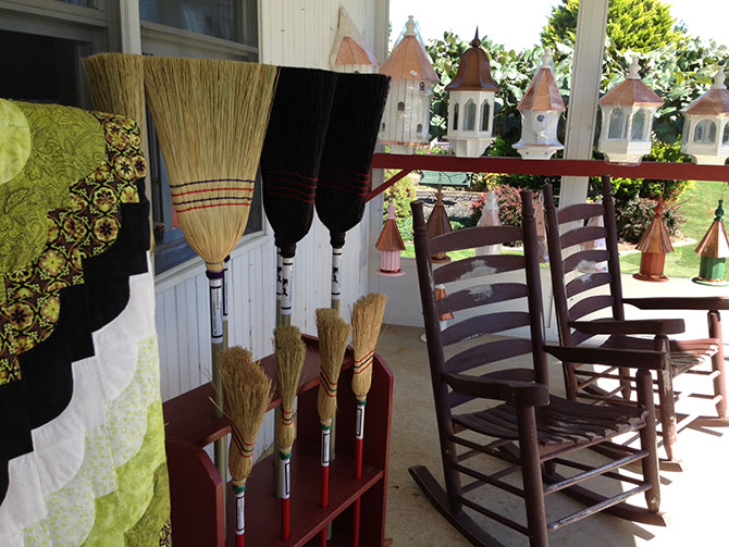 The Inn At Leola Village rocking chairs on porch with handmade brooms and wooden bird houses