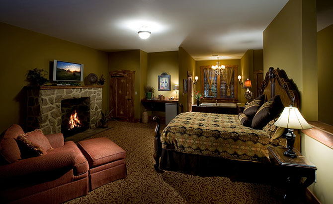 The Inn At Leola Village king guest room with stone fireplace
