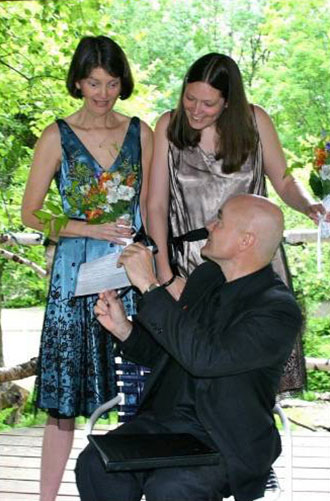 Moose Meadow Lodge - Lesbian couple receiving marriage license from wedding officiant