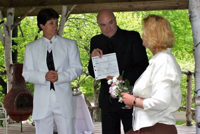 Moose Meadow Lodge - Marriage officiant providing wedding license to lesbian couple